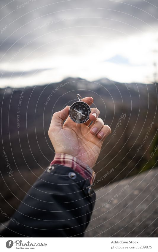 Traveler carrying compass in mountain valley traveler rocky modern hold outstretched hand stand person man adult direction trip tourism navigation geography