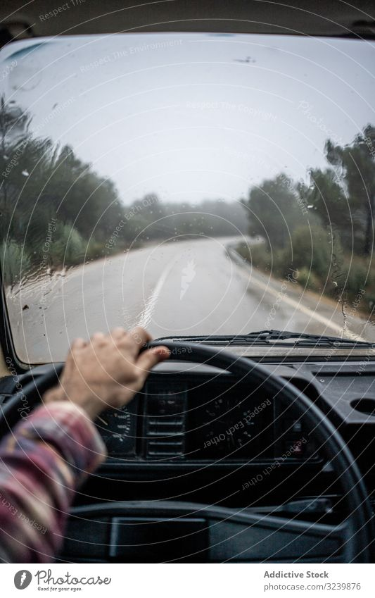 Driver riding car along rural pathway at forest in rain driver autumn man wheel wet road tree evergreen plaid shirt arm cabin adult travel transport lifestyle