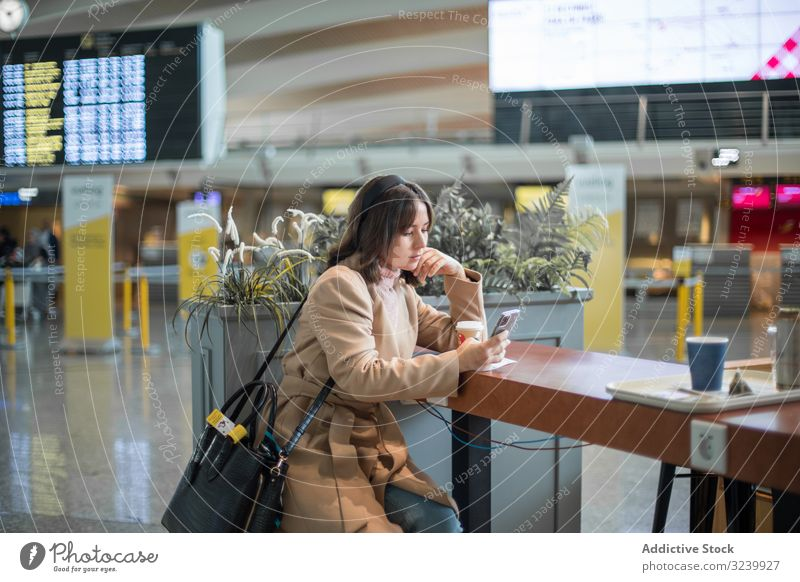 Lady sitting and using smartphone at airport woman waiting room airplane departure traveler coffee browsing terminal mobile watching surfing lifestyle texting