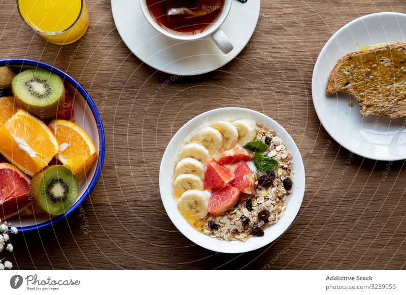 Juice and plate with granola and fruits on table juice buffet meal sliced citrus breakfast strawberry banana tea healthy muesli orange grapefruit served vegan