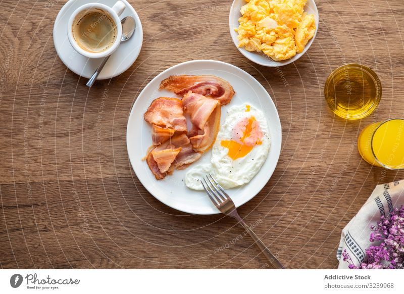 Tasty bacon and eggs with juice at table breakfast food meal served nutrition eating yolk fried healthy variety ingredient fresh appetizing protein tasty pastry