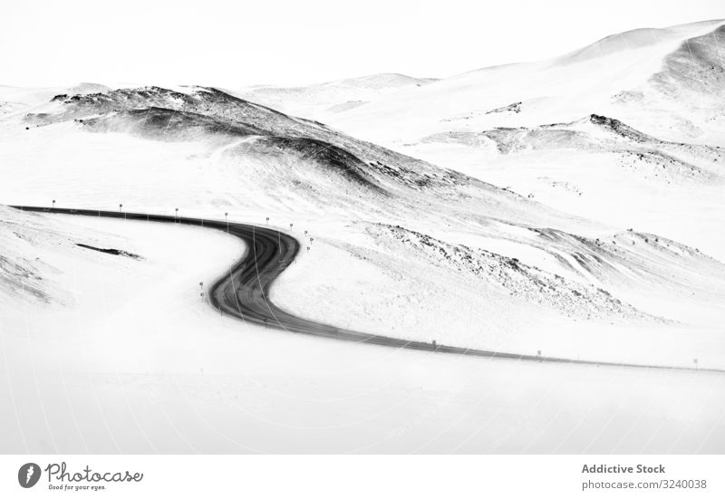 Winding road through snowy hills winter white iceland winding countryside terrain route curvy asphalt path ridge range mountain nature nobody highway frost cold