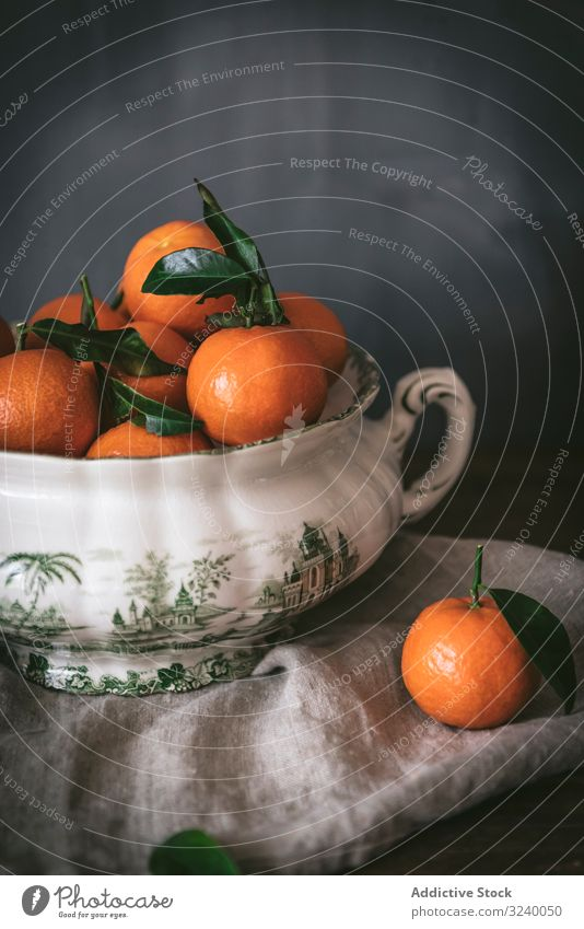Orange tangerines in ceramic ornamental bowl on wooden table sophisticated fruit healthy classic composition still life art fresh juicy organic green tasty food