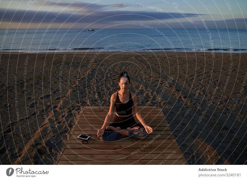 Barefoot woman meditating on wooden path yoga beach asana activity lotus pose fit closed eyes crossed legs female slim sportswear training workout fitness
