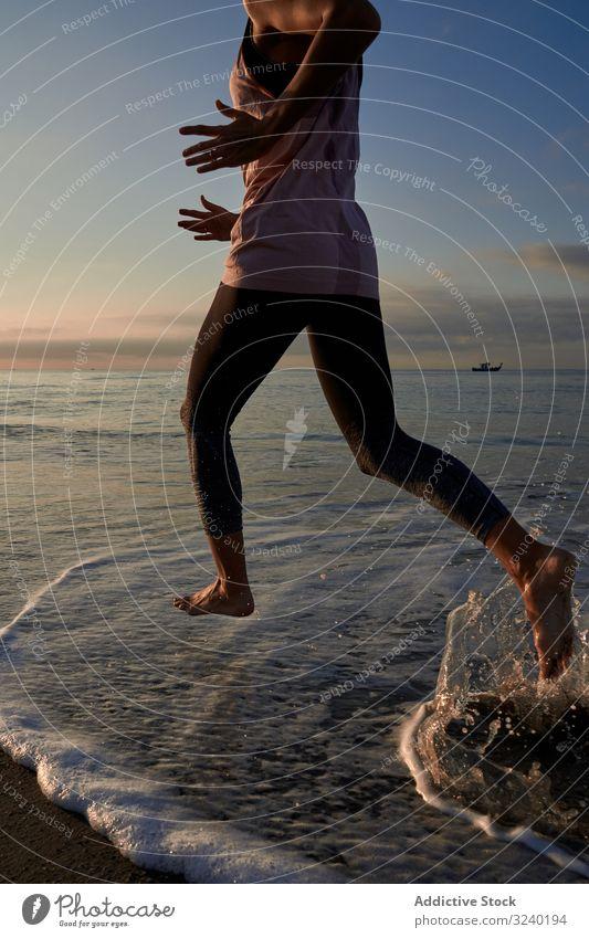 Slim woman jogging on beach run sea evening training fit fitness summer female sport lifestyle athlete barefoot shore coast wave sand water lady cardio athletic
