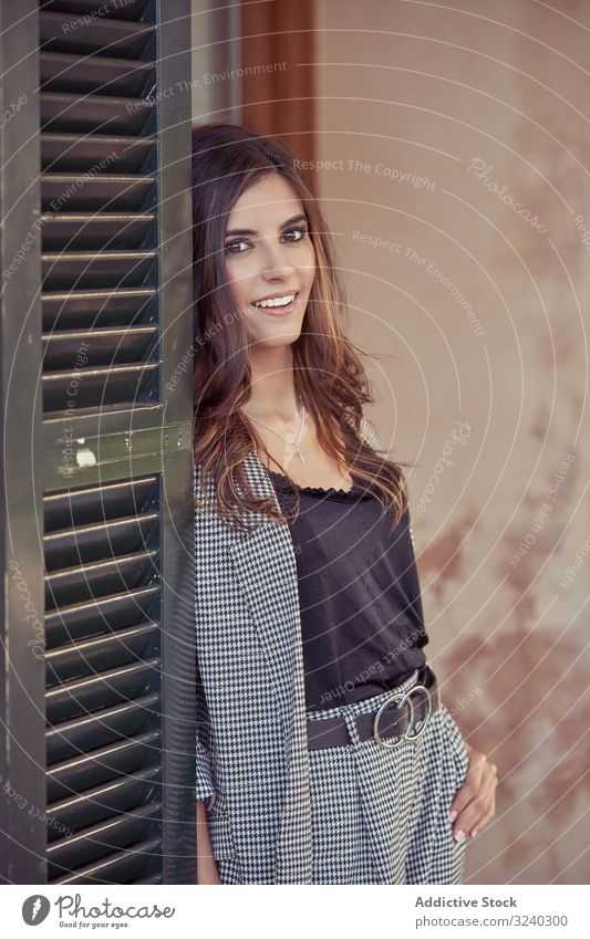 Woman friendly smiling from behind of doorway woman stylish charming natural female cheerful adult young casual relaxing laughing trendy elegant beautiful