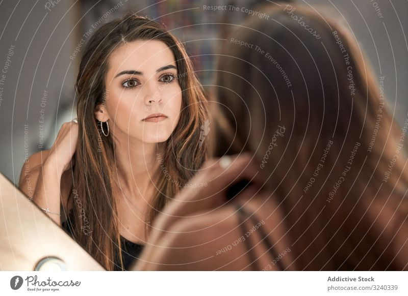 Woman looking at mirror after makeup woman cosmetic salon care reflection treatment equipment style comfortable beauty interior design face long haired modern