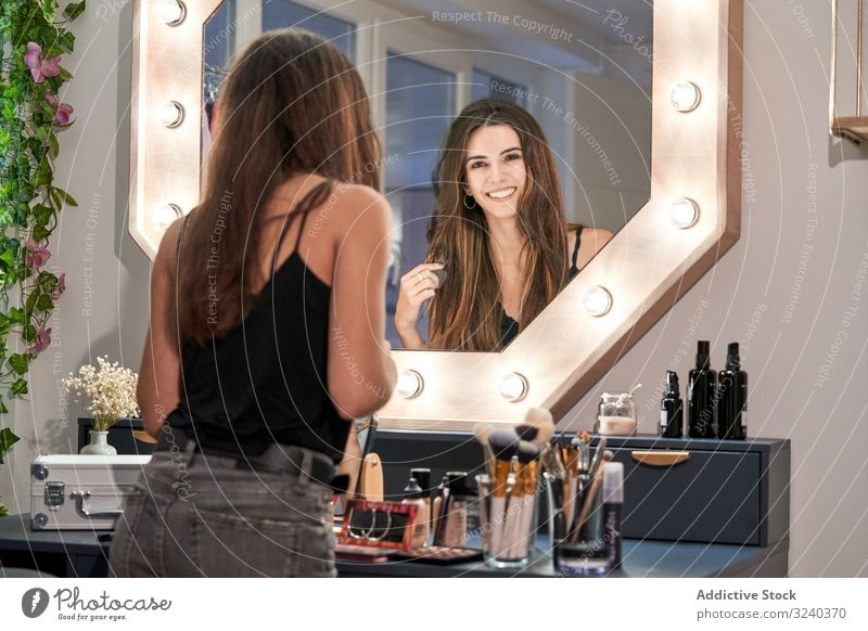 Smiling woman looking at mirror in hand in cosmetic salon reflection smiling makeup care treatment equipment style comfortable beauty interior design face