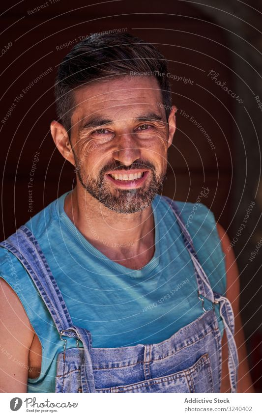 Smiling workman in denim overall looking at camera portrait craftsman worker overalls happy smile middle aged beard cheerful service male professional mechanic