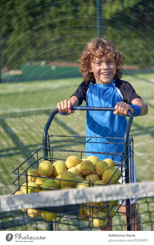 Cheerful boy pushing cart with tennis balls court smile assistant training walk kid child activity game player sport lifestyle practice equipment trolley