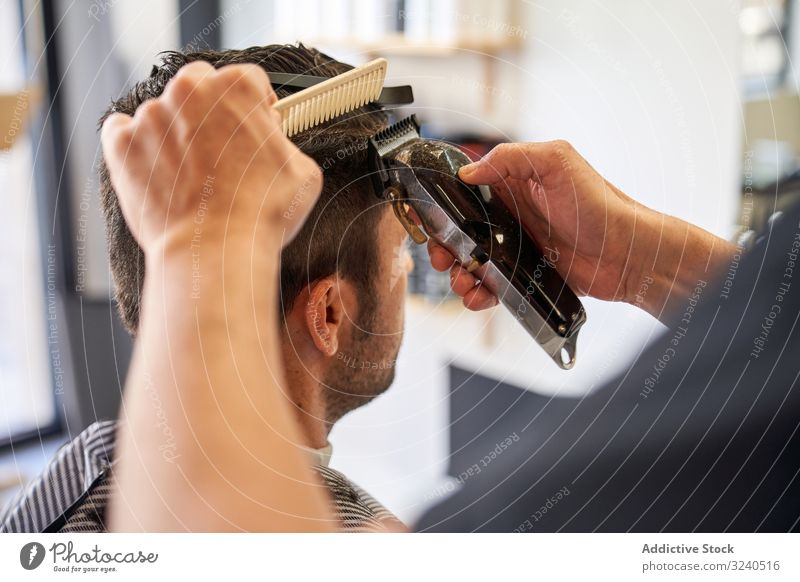 Detail of the hands of a barber cutting hair with a comb and a razor detail shaver barbershop hairstyle work service professional hairdresser arms wet man