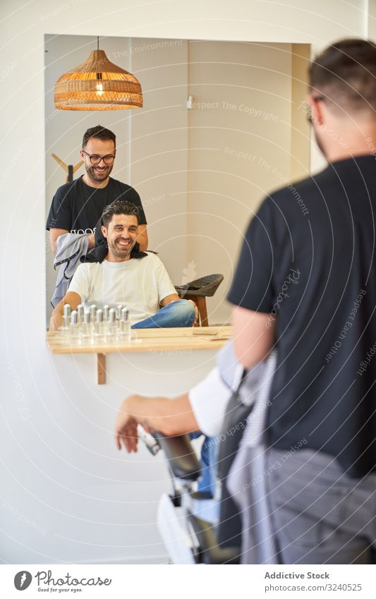 Vertical photo of barber drying hair with a towel to a client in front of a mirror vertical saloon chair products barbershop hairdryer furniture work service