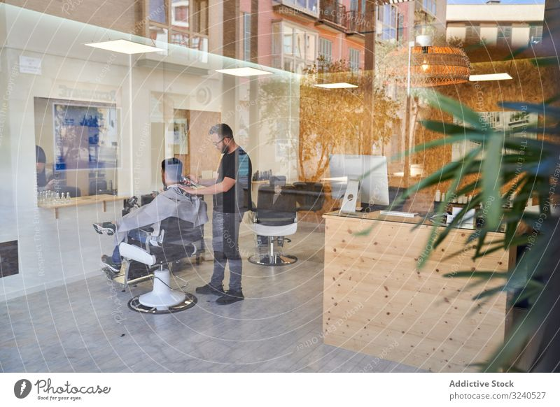 View of a barber shop from outside the enclosure with a barber inside cutting a client's hair design reflexion window storefront street decoration outdoors
