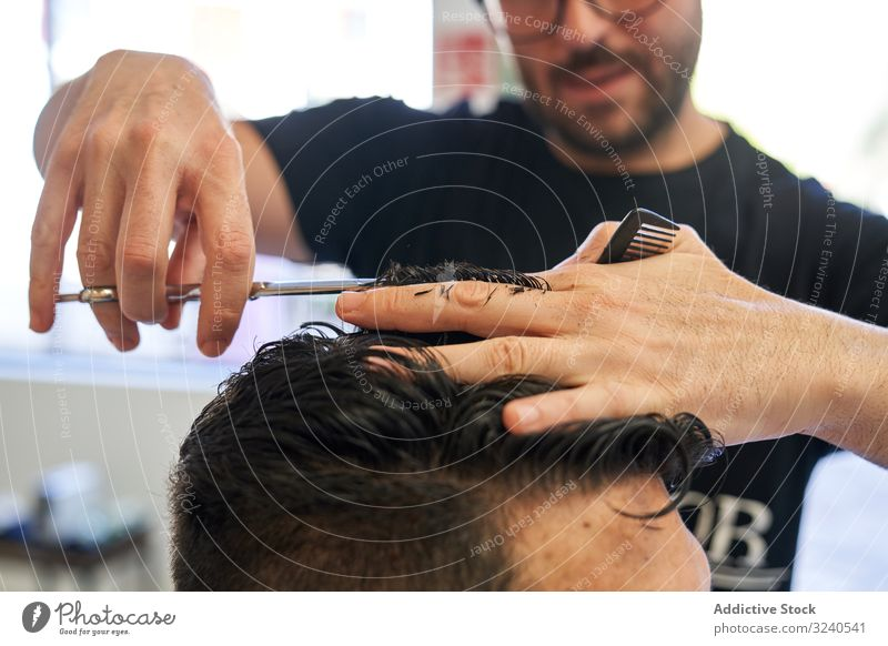 Detail of a hand from a barber cutting hair with scissors and a comb to a customer with the blur in the background haircut salon client hairdressing human