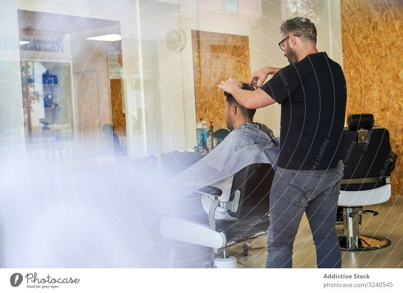 View of a barber shop from outside through fogged glass with a barber inside cutting a client's hair vertical reflexion window storefront street outdoors shaver