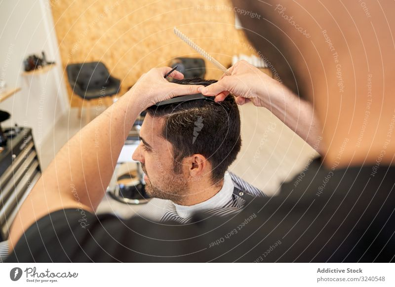 Barber cutting a client's hair sitting on the barbershop couch comb hairstyle furniture work service professional hairdresser hands arms wet man haircare