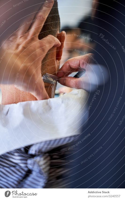 Vertical photo of a detail of a barber's hands cutting a client's hair with a razor vertical handmade vintage nape service mirror reflexion shaver barbershop