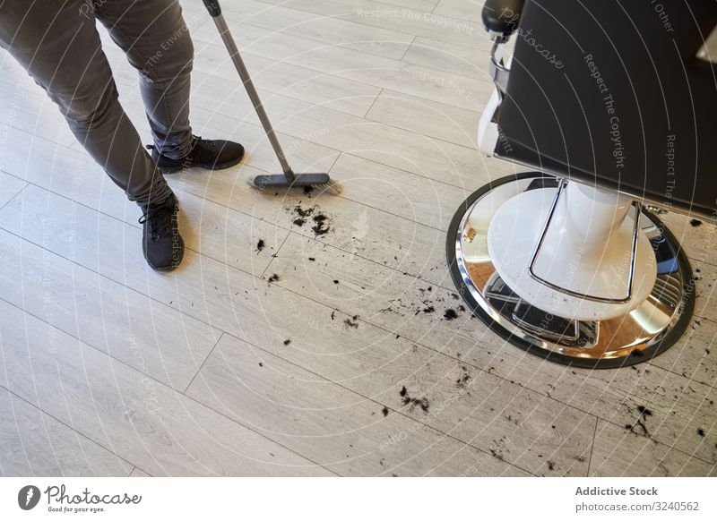 Barber sweeping with the broom the hairs of a customer that are on the wooden floor clipping salon barber barbershop business hairdresser beauty nobody