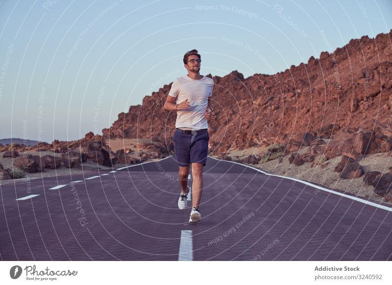 Excited man running on road against mountain landscape journey volcano asphalt surrounded rocky el teide tenerife spain canary island adventure distance sky