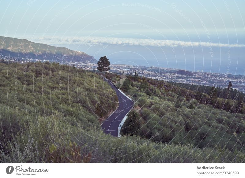 View of road going down to city under mountains town roadway park island volcano tenerife el teide spain landscape scenery asphalt scenic location cityscape
