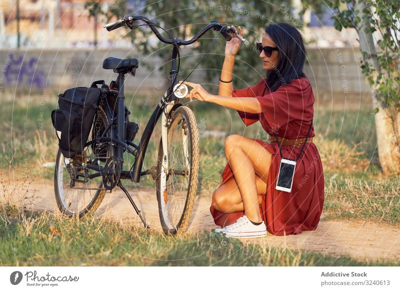 Woman fixing bike in park woman bicycle headlight path casual city summer activity female vehicle repair adjust transport lifestyle rest relax weekend lady