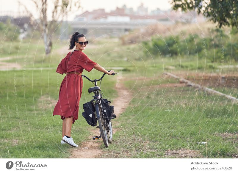 Woman with bicycle walking in park woman path smile casual city summer activity female bike vehicle transport push lifestyle rest relax weekend cheerful lady
