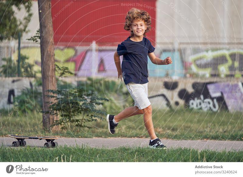 Little skater running in park boy fun skateboard path smile casual city urban lifestyle recreation summer happy joy cheerful kid child way alley childhood