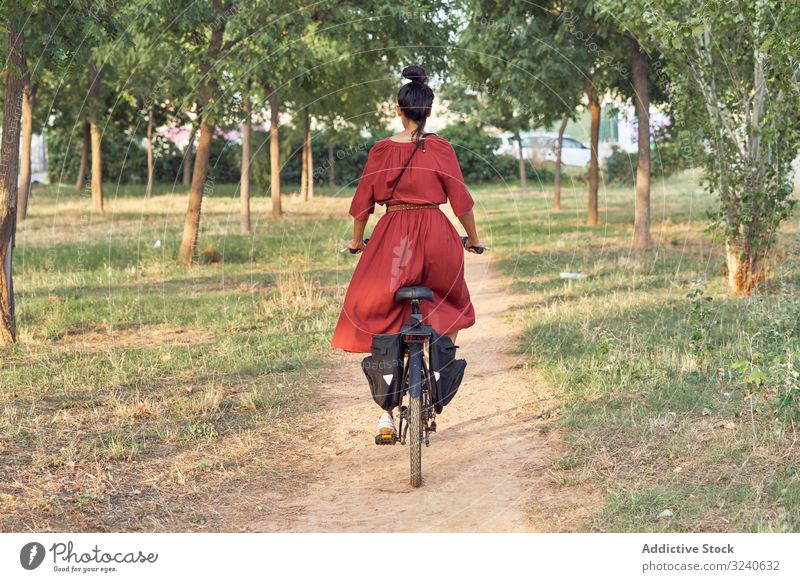 Woman riding bicycle in park woman path smile casual city summer activity female bike vehicle transport lifestyle rest relax weekend cheerful lady dress