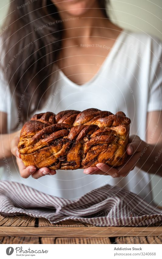 Faceless woman with appetizing cinnamon babka cook bread dessert baked twisted loaf delicious food sweet homemade fresh chocolate cuisine female white t shirt