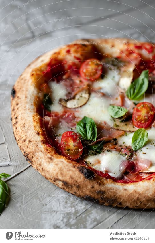 Close up of tasty summer pizza traditional table rustic italian gourmet fresh yummy delicious towel cloth fabric herb basil dinner lunch food appetizing edible