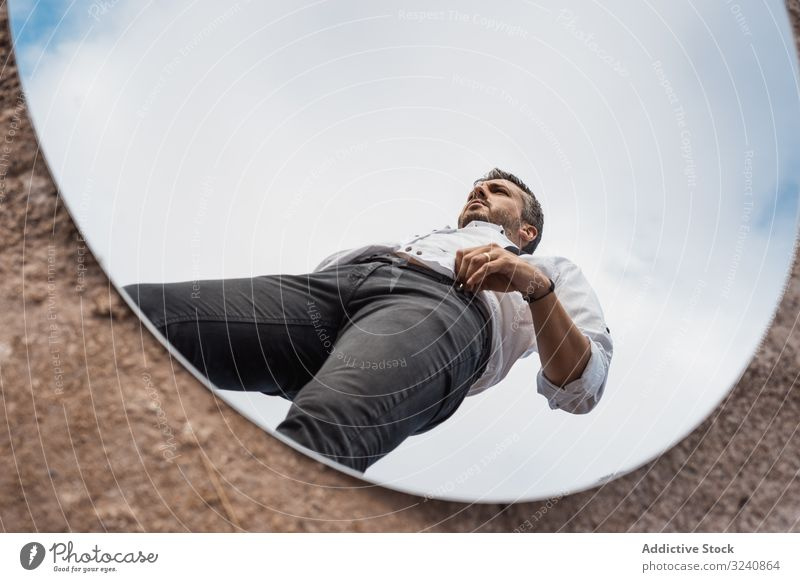 Fancy man reflecting in mirror on ground reflection fancy dreamy white shirt suspenders stand blue sky handsome oval dusty surreal usa concept pensive modern