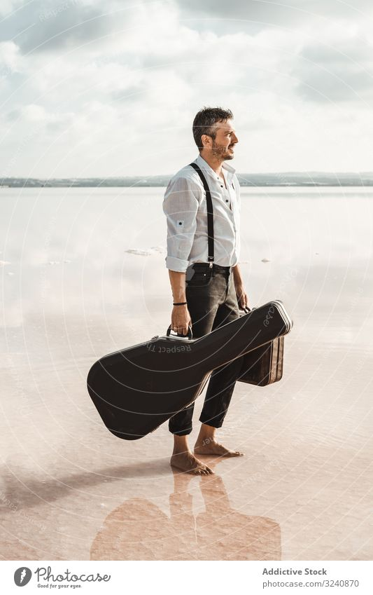 Focused stylish man with suitcase and guitar gig bag on seaside serious barefoot carry water usa shore gazing contemplation modern artist musician young adult