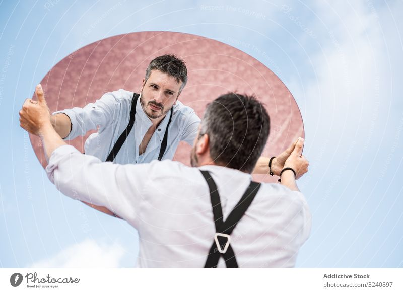 Stylish man holding mirror up and reflecting reflection stylish pensive white shirt suspenders stand blue sky lifting carrying handsome oval surreal usa concept