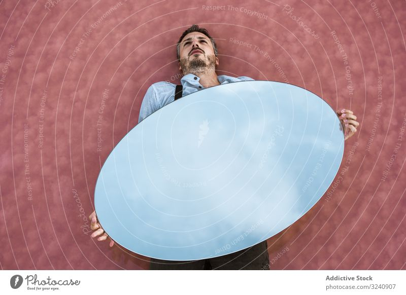 Man lying down holding mirror with reflection man stylish pensive white shirt suspenders blue sky carrying handsome oval surreal concept modern young adult art