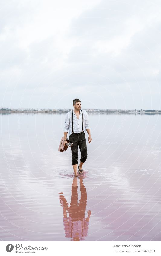 Musician holding guitar at seaside musician inspired barefoot stand play water cloudy man shore white shirt suspenders horizon reflection young guitarist