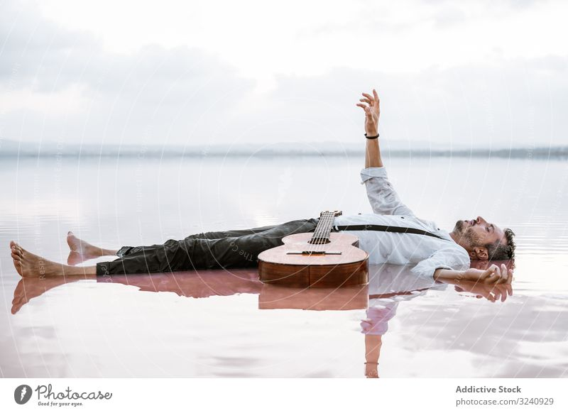 Man resting in water with guitar at seaside man classy lying on back floating sandbank white shirt suspenders dreamy peaceful calm neutral young adult bristle