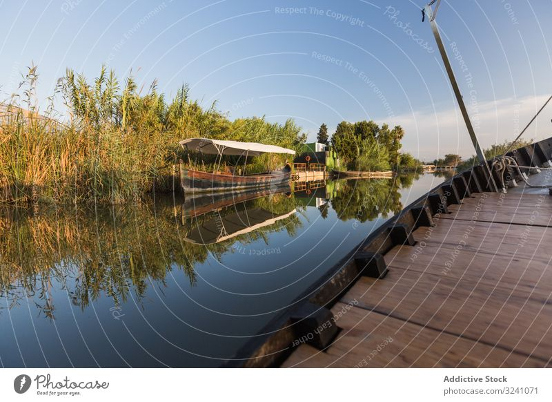 Side of modern boat sailing along rural shore vessel ride tranquil sunny coast lagoon valencia reflection smooth waterfront greenery side detail wooden new