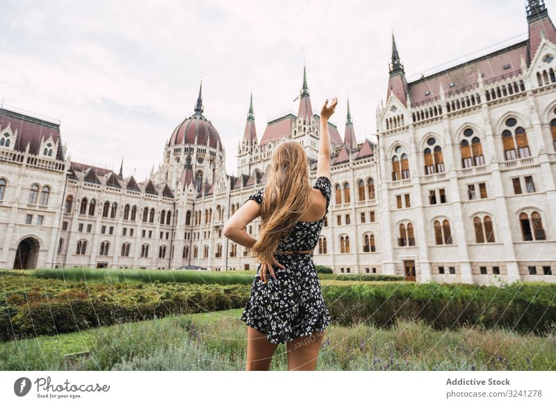 Long haired woman raising hand to ancient old building architecture palace tower tourism explore budapest hungary shape art dome travel urban city geometric