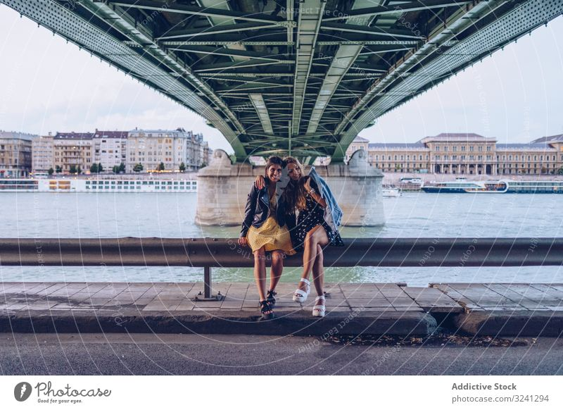 Smiling girlfriends hugging and sitting on fence along river under bridge women travel city tourist architecture fun smiling vacation together tourism budapest