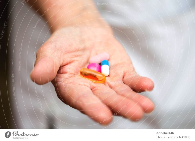 Many multi-colored pills in a Senior's hands. Painful old age. Bottle Health care Medical treatment Illness Medication Hospital Human being Woman Adults Hand