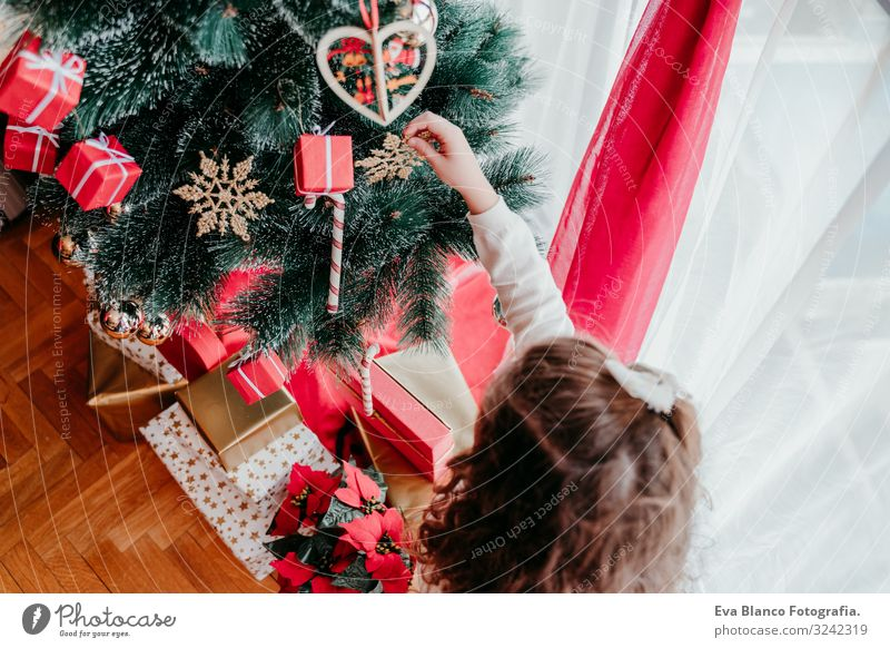 kid girl decorating christmas tree at home Child Human being Vacation & Travel Christmas & Advent Beautiful Green Red Tree House (Residential Structure) Joy