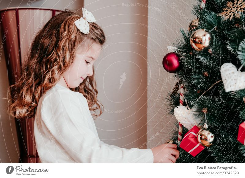kid girl decorating christmas tree at home Child Human being Christmas & Advent Beautiful Green Red Tree House (Residential Structure) Joy Winter Girl Lifestyle