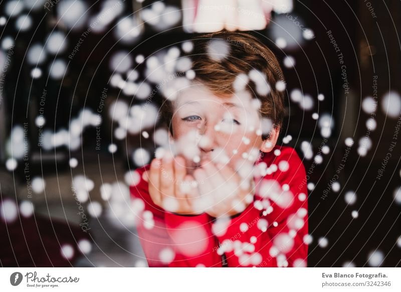 young boy blowing artificial snow flakes at home. Christmas Child Human being Vacation & Travel Beautiful White Red House (Residential Structure) Joy Winter