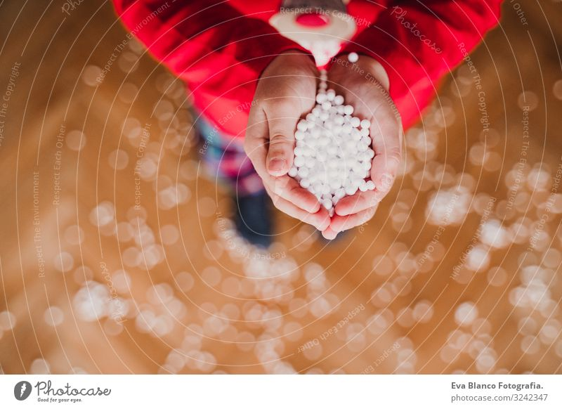 Kid holding artificial snow flakes at home Child Human being Beautiful White Red Hand House (Residential Structure) Joy Winter Girl Snow Boy (child) Small