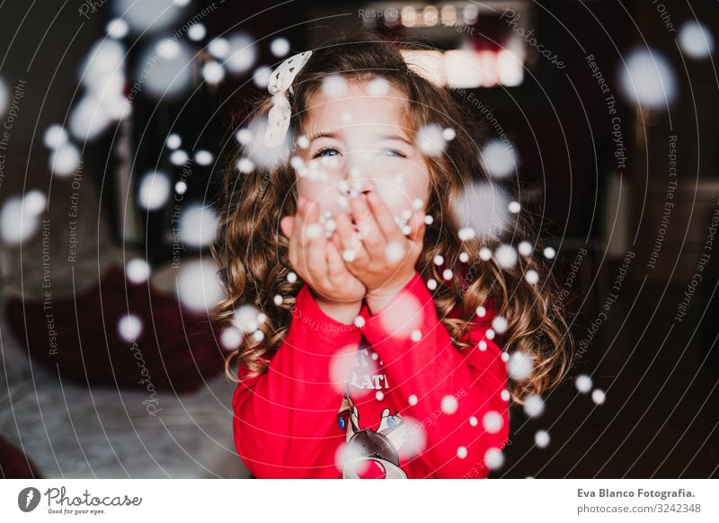 young girl blowing artificial snow flakes at home. Christmas Joy Beautiful Playing Winter Snow House (Residential Structure) Christmas & Advent Child Feminine