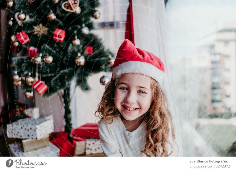 portrait of beautiful kid girl at home by the christmas tree Child Human being Beautiful Red Tree House (Residential Structure) Calm Joy Winter Girl Window