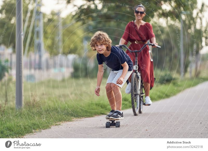 Mother and son riding along park path mother ride skateboard bicycle together fun family happy boy woman child kid summer joy glad pleasure smile cheerful