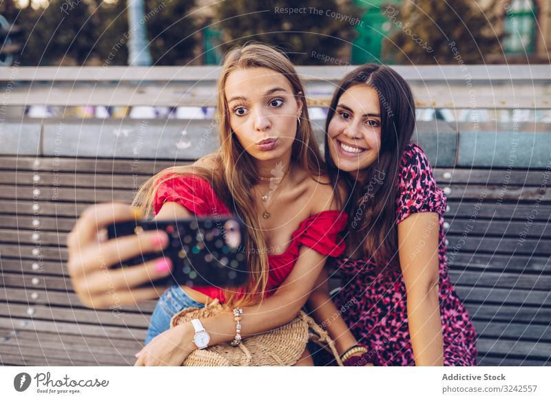 Laughing women taking selfie on wooden bench at street travel city memory using architecture building smartphone happy budapest friend friendship relationship