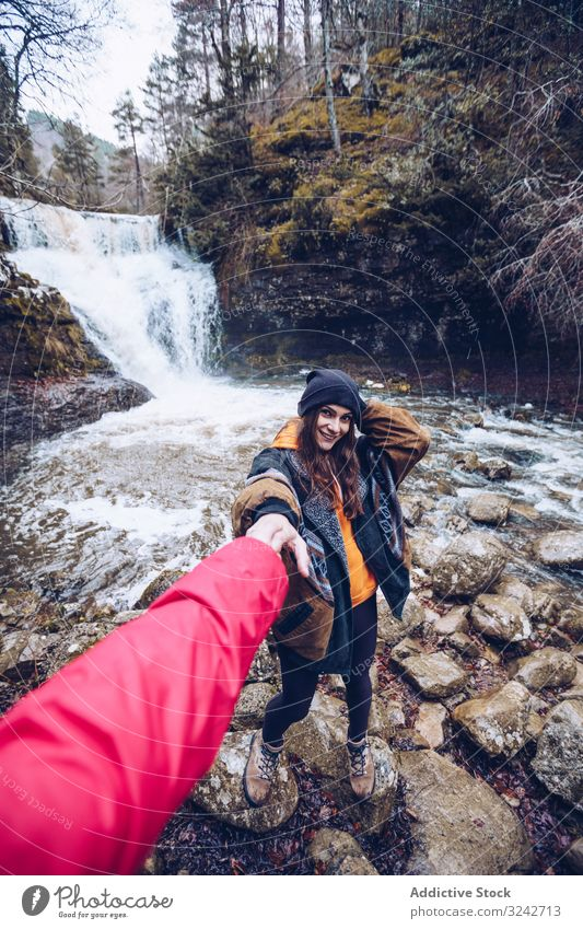 Woman leading by hand person to mountain waterfall woman following walk hold cold forest pond cascade evergreen chill follow me young adult attractive tourist