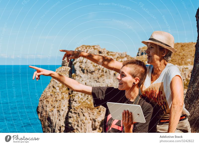 Stylish woman with tablet in hands and elderly lady pointing with finger to blue sea women mature rocky using water sky vacation summer ocean happy tropical